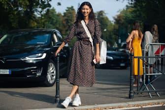MILAN, ITALY - SEPTEMBER 22: Model Hoyeon Jung wears a floral dress, bellboy bag, and white sneakers during Milan Fashion Week Spring/Summer 2019 on September 22, 2018 in Milan, Italy.