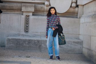 PARIS, FRANCE - SEPTEMBER 30: Model Hoyeon Jung wears a pink/purple print shirt, oversized blue jeans, a Chanel black leather bag, and red purple sneakers after the Poiret show during Paris Fashion Week Spring/Summer 2019 on September 30, 2018 in Paris, France. (Photo by Melodie Jeng/Getty Images)