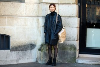 PARIS, FRANCE - FEBRUARY 28: Korean model Hoyeon Jung wears an all-black outfit including an oversized leather jacket, a down jacket, a turtleneck, stockings, combat boots, and a tan Comme des Garcons  Shirt paper/plastic tote bag on February 28, 2018 in Paris, France. (Photo by Melodie Jeng/Getty Images)