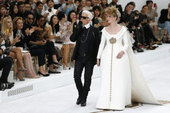 German fashion designer Karl Lagerfeld acknowledges the public with a model at the end of the Chanel 2014/2015 Haute Couture Fall-Winter collection fashion show on July 8, 2014 at the Grand Palais in Paris.  AFP PHOTO / PATRICK KOVARIK        (Photo credit should read PATRICK KOVARIK/AFP via Getty Images)
