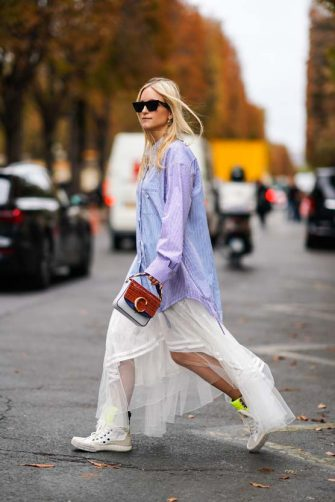 PARIS, FRANCE - SEPTEMBER 26: Charlotte Groeneveld wears sunglasses, a white and blue striped oversized shirt, a  ruffled flowing white lace skirt, white sneakers, a red crocodile pattern Chloe handbag, outside Chloe, during Paris Fashion Week - Womenswear Spring Summer 2020 on September 26, 2019 in Paris, France. (Photo by Edward Berthelot/Getty Images)