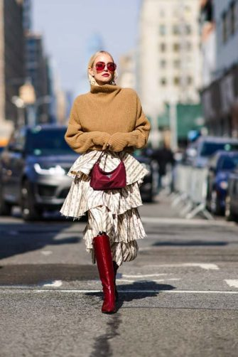 NEW YORK, NEW YORK - FEBRUARY 09: Leonie Hanne wears a brown turtleneck wool oversized pullover, a purple Prada bag, a ruffled skirt, burgundy leather high pointy boots, outside Brock Collection, during New York Fashion Week Fall Winter 2020, on February 09, 2020 in New York City. (Photo by Edward Berthelot/Getty Images)