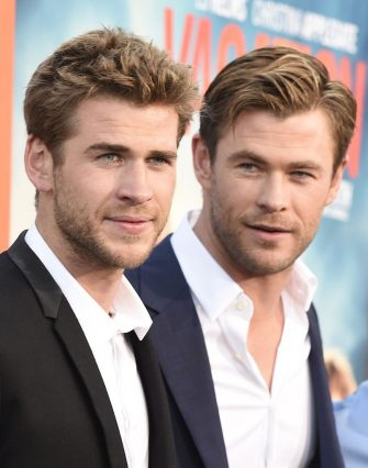 "Actors Liam Hemsworth (L) and Chris Hemsworth arrive for the premiere of Warner Bros' ""Vacation"" at the Regency Village Theatre in Los Angeles on July 27, 2015. AFP PHOTO/ROBYN BECK        (Photo credit should read ROBYN BECK/AFP via Getty Images)"