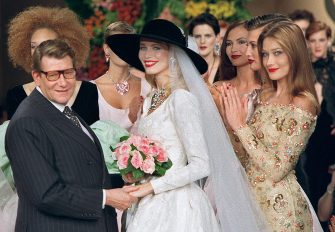 Photo taken on July 10, 1996 shows French fashion designer Yves Saint Laurent (L) posing with models Claudia Schiffer (C) and Carla Bruni during the presentation of the autumn-winter 96/97 haute couture collection in Paris. Saint Laurent, widely hailed as one of the greatest designers of the 20th century, died on June 1, 2008 in Paris. He was 71. AFP PHOTO PIERRE VERDY (Photo credit should read PIERRE VERDY/AFP via Getty Images)