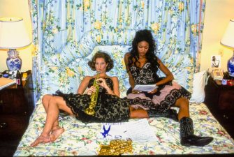 UNITED STATES - FEBRUARY 1:  Models, Naomi Campbell (right) and Christy Turlington sitting on bed from a room at the Pontchatrain Hotel in New Orleans LA, wearing black lace bustiers and skirts by Louis Dell'Olio for Anne Klein  CREDIT MUST READ: Arthur Elgort/Conde Nast via Getty Images. (Photo by Arthur Elgort/Conde Nast via Getty Images)
