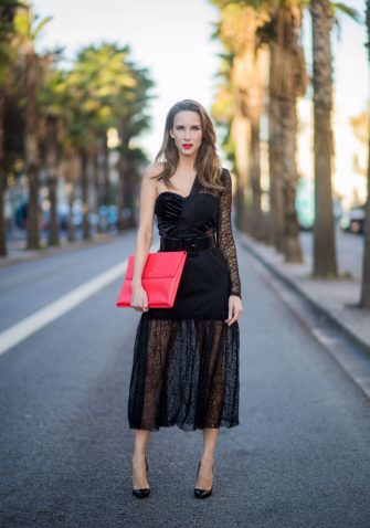 BARCELONA, SPAIN - NOVEMBER 29: Alexandra Lapp wearing a black asymmetric shoulder dress with a delicate floral lace and a velvet fitted bustier from Three Floor, Pigalle Christian Louboutin black patent leather heels and a simple MCM pouch in marigold orange on November 29, 2017 in Barcelona, Spain. (Photo by Christian Vierig/Getty Images)