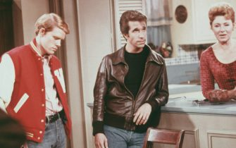 Left to right: American actors Henry Winkler, as Arthur 'Fonzie' Fonzarelli, Ron Howard as Richie Cunningham, and Marion Ross as Marion Cunningham, in a scene from the television sitcom 'Happy Days', circa 1975. (Photo by Fotos International/Hulton Archive/Getty Images)
