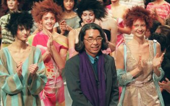 Japanese fashion designer Kenzo walks on the stage among his models, 16 October in Paris, at the end of his Spring/Summer 1999 ready-to-wear collection show. (Photo by Thomas COEX / AFP) (Photo by THOMAS COEX/AFP via Getty Images)