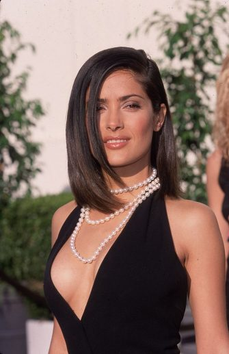 9th May 2000:  Mexican actor Salma Hayek smiles while posing outdoors at the 6th Annual Blockbuster Entertainment Awards, Shrine Auditorium, Los Angeles, California. Hayek won Favorite Supporting Actress - Action for her work in director Barry Sonnenfeld's film 'Wild Wild West.' She wears a black dress with a plunging neckline and a pearl necklace.  (Photo by Paul Skipper/Fotos International/Getty Images)