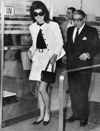 (Original Caption) Wearing mod sunglasses and a miniskirt, Jacqueline Kennedy Onassis accompanies her husband, Aristotle, to a plane at Kennedy Airport on today, before the Greek shipping magnate took off for Athens. Ari was flying his own Olympic Airways to Europe and Jackie came along to the airport to say goodbye.