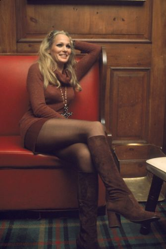 Swiss motion picture actress Ursual Andress sits on a red leather couch in a miniskirt, high boots, and turtleneck sweater with her legs crossed, 1970s. (Photo by Tim Boxer/Getty Images)