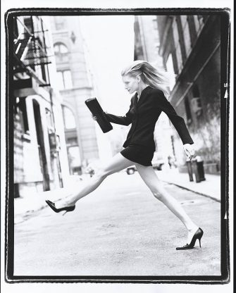 UNITED STATES - AUGUST 1:  Model Kirsten Owen wearing a black asymmetrical jacket and a short straight narrow black skirt, by Michael Kors, walking with long strides across a city street  CREDIT MUST READ: Arthur Elgort/Conde Nast via Getty Images. (Photo by Arthur Elgort/Conde Nast via Getty Images)