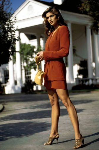 Vogue, March 1992 - Model Cindy Crawford posed on a driveway with a white columned portico in the background. She is wearing a red silk suit with soft draped jacket and a miniskirt by Giorgio Armani. Accessories: suede sandals by Maude Frizon; bag by Paloma Picasso. Hair by Christiaan. Makeup by Sonia Kashuk for Aveda. (Arthur Elgort/Conde Nast via Getty Images)