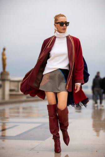 PARIS, FRANCE - JANUARY 23: Elina Halimi, wearing a white jumper, brown and black mini skirt, burgundy boots, burgundy coat and scarf, is seen outside Elie Saab show during Paris Fashion Week - Haute Couture Spring Summer 2019 on January 23, 2019 in Paris, France. (Photo by Claudio Lavenia/Getty Images)