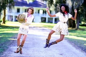 UNITED STATES - FEBRUARY 1:  Models, Naomi Campbell (right) and Christy Turlington, kicking up their heels in front of the Parlange plantation outside New Orleans, wearing embroidered outfits by Todd Oldham CN00053616. CREDIT MUST READ: Arthur Elgort/Conde Nast via Getty Images. (Photo by Arthur Elgort/Conde Nast via Getty Images)