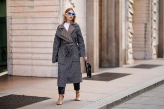 MILAN, ITALY - FEBRUARY 20: Dagmara Jarzynka wears blule sunglasses, a gray oversized long coat with checked inner lining, a white top, a black shiny bag, pale brown leather boots, outside Vivetta, during Milan Fashion Week Fall/Winter 2020-2021 on February 20, 2020 in Milan, Italy. (Photo by Edward Berthelot/Getty Images)