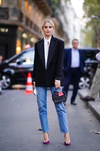 PARIS, FRANCE - SEPTEMBER 28: Caroline Daur wears a white shirt, a black blazer jacket, a bag with an attached pink mini bag, blue cropped jeans, purple shoes, outside Ralph Lauren, during Paris Fashion Week - Womenswear Spring Summer 2020 on September 28, 2019 in Paris, France. (Photo by Edward Berthelot/Getty Images)