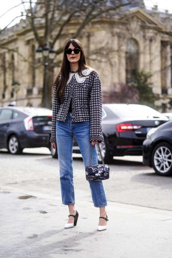 PARIS, FRANCE - MARCH 03: Leia Sfez wears sunglasses, a tweed checked pattern jacket with white embroidered collar, blue denim jeans, a Chanel bag, pointy shoes outside Chanel, during Paris Fashion Week - Womenswear Fall/Winter 2020/2021 on March 03, 2020 in Paris, France. (Photo by Edward Berthelot/Getty Images)