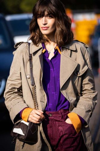 MILAN, ITALY - SEPTEMBER 24: Greta Ferro, wearing a beige trench coat, purple shirt, burgundy pants and Tod's bag, poses ahead of the Tod's fashion show during the Milan Fashion Week - Spring / Summer 2022 on September 24, 2021 in Milan, Italy. (Photo by Claudio Lavenia/Getty Images)