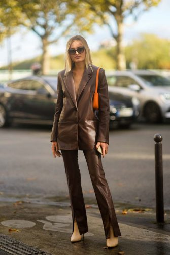 PARIS, FRANCE - OCTOBER 05: A guest wears sunglasses, a brown shiny leather blazer jacket, brown shiny leather slit / split flared pants, an orange shiny grained leather shoulder bag, beige leather pointed heels ankle shoes, rings, outside Lacoste, during Paris Fashion Week - Womenswear Spring Summer 2022, on October 05, 2021 in Paris, France. (Photo by Edward Berthelot/Getty Images)