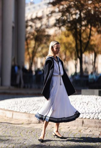 PARIS, FRANCE - OCTOBER 05: Fashion Week Guest wearing a white dress and a black cardigan and black heels outside Miu Miu Show on October 05, 2021 in Paris, France. (Photo by Jeremy Moeller/Getty Images)