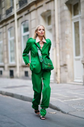 PARIS, FRANCE - OCTOBER 15: Leonie Hanne wears a pink shirt with a large collar, a green blazer jacket with shoulder pads, a green leather Givenchy bag with printed snake pattern, green pants, black shoes, in the streets of Paris, on October 15, 2019 in Paris, France. (Photo by Edward Berthelot/Getty Images)