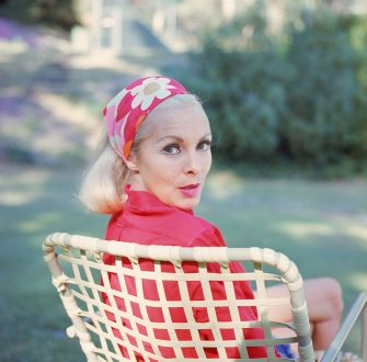 American actress Janet Leigh (1927 - 2004) looks over her shoulder as she sits in a lawn chair and wears a red floral print headscarf, late 1960s. (Photo by Hulton Archive/Getty Images)