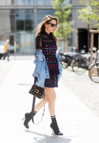 BERLIN, GERMANY - JULY 06: Alexandra Lapp (model, blogger) wearing a mini lace dress in navy blue and heady red from Self-Portrait, a Roger Viv mini bag crafted in suede with waterjet cut Guipure detailing, flap, clasp fastening, metal buckle and details, handle and leather removable strap in trapezium shape and ankle boots from Roger Vivier in black patent leather, denim jacket by SET, brown sunglasses with pearls by Chanel and Fendi during the Mercedes-Benz Fashion Week Berlin Spring/Summer 2018 on July 6, 2017 in Berlin, Germany. (Photo by Christian Vierig/Getty Images)