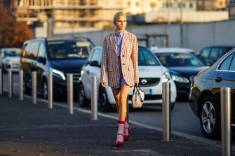 MILAN, ITALY - JANUARY 12: Caroline Daur wears a checked oversized blazer jacket, a Prada white and black bag, pink wool socks, red shoes, a blue striped shirt, outside Prada, during Milan Fashion Week Menswear Fall/Winter 2020/2021, on January 12, 2020 in Milan, Italy. (Photo by Edward Berthelot/Getty Images)