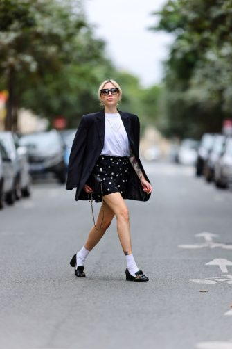 PARIS, FRANCE - JULY 16: Emy venturini wears sunglasses from Dita Eyewear, earrings, a black oversized blazer jacket from Prada, a white t-shirt from The Frankie Shop, a necklace, black mini shorts with printed polka dots from Marc Jacobs, white socks from Calzedonia, Gucci leather loafers shoes, a black leather quilted Chanel bag, on July 16, 2021 in Paris, France. (Photo by Edward Berthelot/Getty Images)
