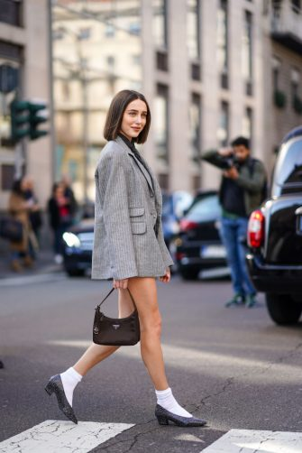 MILAN, ITALY - FEBRUARY 22: Mary Leest wears a gray oversized jacket, a Prada bag, white socks, pointy shoes, a tie, outside Ermanno Scervino, during Milan Fashion Week Fall/Winter 2020-2021 on February 22, 2020 in Milan, Italy. (Photo by Edward Berthelot/Getty Images)
