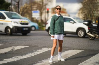 PARIS, FRANCE - MARCH 03: Sophia Roe wears sunglasses, a white polo shirt, a green pullover from Lacoste, a white pleated mini skirt, white socks, sneakers, outside Lacoste, during Paris Fashion Week - Womenswear Fall/Winter 2020/2021 on March 03, 2020 in Paris, France. (Photo by Edward Berthelot/Getty Images)