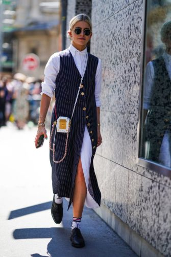 PARIS, FRANCE - JUNE 22: Caroline Daur wears sunglasses, a white long shirt dress, a sleeveless striped long jacket, a mini bag with golden inserts, striped socks, black shoes, outside Thom Browne, during Paris Fashion Week - Menswear Spring/Summer 2020, on June 22, 2019 in Paris, France. (Photo by Edward Berthelot/Getty Images)