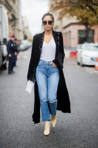 PARIS, FRANCE - OCTOBER 02: Aimee Song with braids hair, wearing denim jeans, black coat seen outside Sacai during Paris Fashion Week Spring/Summer 2018 on October 2, 2017 in Paris, France. (Photo by Christian Vierig/Getty Images)