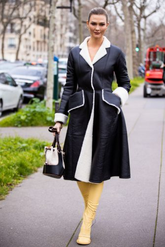 PARIS, FRANCE - FEBRUARY 28: Karlie Kloss, wearing a black leather coat, Loewe bag and yellow boots, is seen outside Loewe, during Paris Fashion Week - Womenswear Fall/Winter 2020/2021 : Day Five on February 28, 2020 in Paris, France. (Photo by Claudio Lavenia/Getty Images)