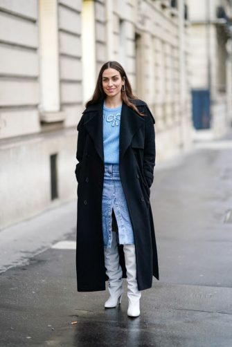 PARIS, FRANCE - FEBRUARY 28: Erika Boldrin wears a dark long coat, a blue pullover, a blue denim skirt, white leather long boots, outside Alessandra Rich, during Paris Fashion Week - Womenswear Fall/Winter 2020/2021, on February 28, 2020 in Paris, France. (Photo by Edward Berthelot/Getty Images)