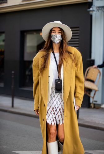 PARIS, FRANCE - OCTOBER 04: Estelle Chemouny seen wearing hat, beige coat, skirt, white boots, blazer, micro Prada bag outside Paco Rabanne during Paris Fashion Week - Womenswear Spring Summer 2021 : Day Seven on October 04, 2020 in Paris, France. (Photo by Christian Vierig/Getty Images)