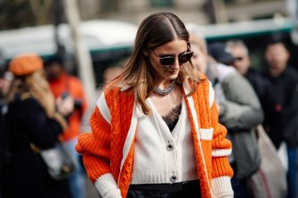 PARIS, FRANCE - MARCH 05: Olivia Palermo wears an orange wool knitted jacket, black flared pants, sunglasses, outside Miu Miu, during Paris Fashion Week Womenswear Fall/Winter 2019/2020, on March 05, 2019 in Paris, France. (Photo by Edward Berthelot/Getty Images)