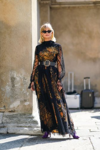 MILAN, ITALY - SEPTEMBER 20:  Xenia Adonts wears sunglasses, a black lace mesh dress with yellow floral print and embroidery, a black large leather belt outside the Etro show during Milan Fashion Week Spring/Summer 2020 on September 20, 2019 in Milan, Italy. (Photo by Edward Berthelot/Getty Images)