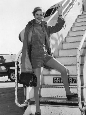 20th March 1967:  British fashion model Twiggy, wearing green shorts and blue tights under an orange coat waves from the aircraft steps at London Airport on her way to the USA.  (Photo by Central Press/Getty Images)