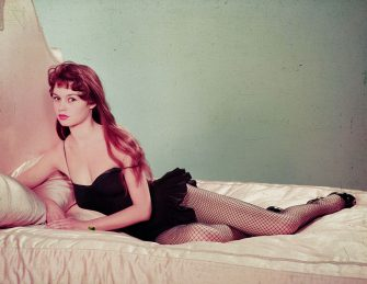 (Original Caption) Full-length portrait of actress and sex symbol Brigitte Bardot, reclining on bed wearing a black teddy with fishnet stockings.