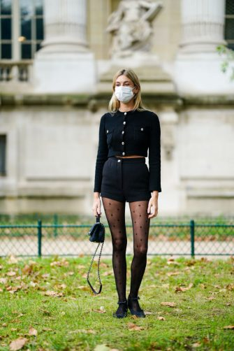 PARIS, FRANCE - OCTOBER 06: Camille Charriere wears a black cardigan with buttons, a black short skirt, tights, a Chanel bag, a white protective face mask, outside Chanel, during Paris Fashion Week - Womenswear Spring Summer 2021, on October 06, 2020 in Paris, France. (Photo by Edward Berthelot/Getty Images)