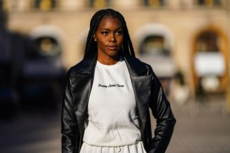 PARIS, FRANCE - FEBRUARY 27: Magalie Kab wears a black leather long coat, a white pullover from Pretty Little Things, white jogger sportswear pants, on February 27, 2021 in Paris, France. (Photo by Edward Berthelot/Getty Images)