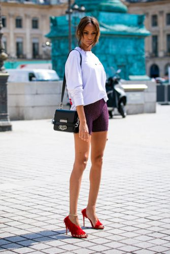 PARIS, FRANCE - JULY 01: Model Joan Smalls, wearing a printed white top, decorated biker shorts, red heels and black Dsquared bag, is seen outside Dundas show during Paris Fashion Week - Haute Couture Fall/Winter 2019/2020 on July 01, 2019 in Paris, France. (Photo by Claudio Lavenia/Getty Images)