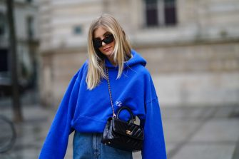 PARIS, FRANCE - MARCH 11: Xenia Adonts wears sunglasses from Linda Farrow, a bold blue hoodie sweater from Cherry LA, a black leather quilted Chanel bag, blue denim baggy jeans with side cargo pockets from Miu Miu, on March 11, 2021 in Paris, France. (Photo by Edward Berthelot/Getty Images)