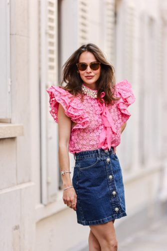PARIS, FRANCE - JUNE 08: Therese Hellström wears sunglasses, a transparent pink puffy sleeves shirt with flowers embroideries and knotted scarf, and white pearls on the collar, a silver and gold watch, blue denim jeans buttoned skirt, silver and rhinestones bracelets, gold rings, a gold Juste Un Clou ring from Cartier, on June 08, 2021 in Paris, France. (Photo by Edward Berthelot/Getty Images)
