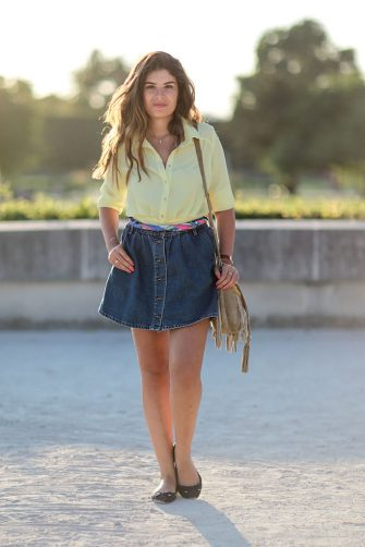 PARIS, FRANCE - AUGUST 20:  Insaf Bennis (fashion blogger - Sparkles in Paris), is wearing a Zara blue denim jeans skirt, a Hanout Boutique bag, a Belbo yellow shirt, and Marwa black shoes, at the Jardin des Tuileries on August 20, 2016 in Paris, France.  (Photo by Edward Berthelot/Getty Images)