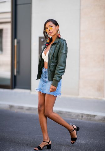 BERLIN, GERMANY - AUGUST 13: Karina Ferreira Flores wearing cropped top, olive green jacket, denim jeans skirt, black sandals, mini sunglasses, statement earrings on August 13, 2018 in Berlin, Germany. (Photo by Christian Vierig/Getty Images)