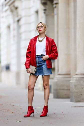 PARIS, FRANCE - MAY 20: Emy Venturini wears Prada sunglasses, gold earrings, a red shiny leather oversized vintage jacket, a gold large chain necklace, a white T-shirt from ipsilonparis, a gold ring, a beige and brown pattern fabric Agnona clutch, blue denim jeans ripped shorts from Redone, red shiny leather pointed ankle pumps heels shoes from Sergio Rossi, on May 20, 2021 in Paris, France. (Photo by Edward Berthelot/Getty Images)
