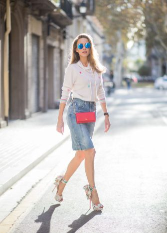 BARCELONA, SPAIN - NOVEMBER 27: Alexandra Lapp wearing a white cashmere hoodie with colored flower applications from Heartbreaker, high rise jeans skirt with slit Adriano Goldschmied, red little purse bag with gold chain from Christian Louboutin, peep-toe pump Christian Louboutin with a long satin bow, sunglasses with round blue shades from Mykita on November 27, 2017 in Barcelona, Spain. (Photo by Christian Vierig/Getty Images)